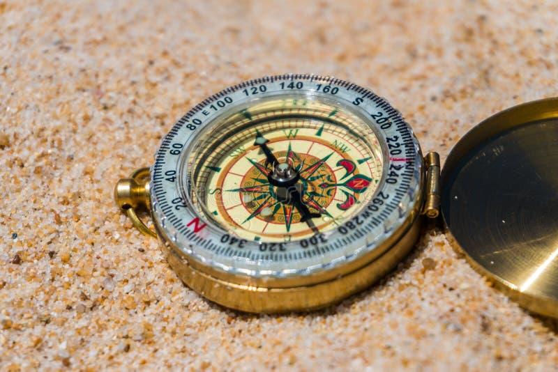 Kompas w piasku na plaży młodzi dorośli obraz stock