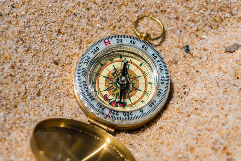 Kompas w piasku na plaży młodzi dorośli zdjęcie stock
