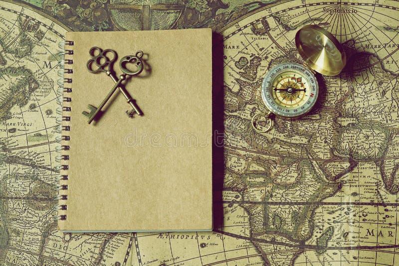 Kompass, antike Schlüssel und Notizbuch auf Unschärfeweinleseweltkarte, Reisekonzept, Kopienraum stockfotos