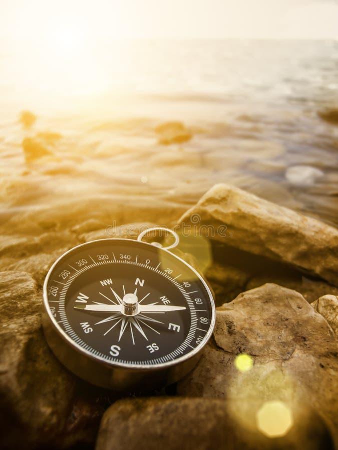 Kompass auf dem Ufer bei Sonnenaufgang stockfotografie