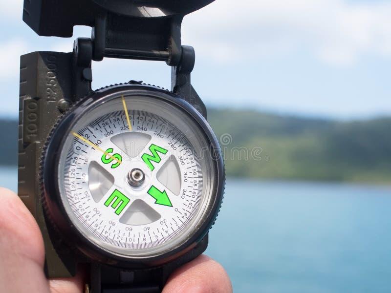 Kompass i handelsresandehanden som söker riktning på fartyget med bakgrund av havet nära kustlinjen och ön (selektiv fokus) royaltyfria foton