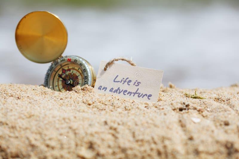 Kompass im Sand mit Mitteilung - das Leben ist ein Abenteuer stockfotografie