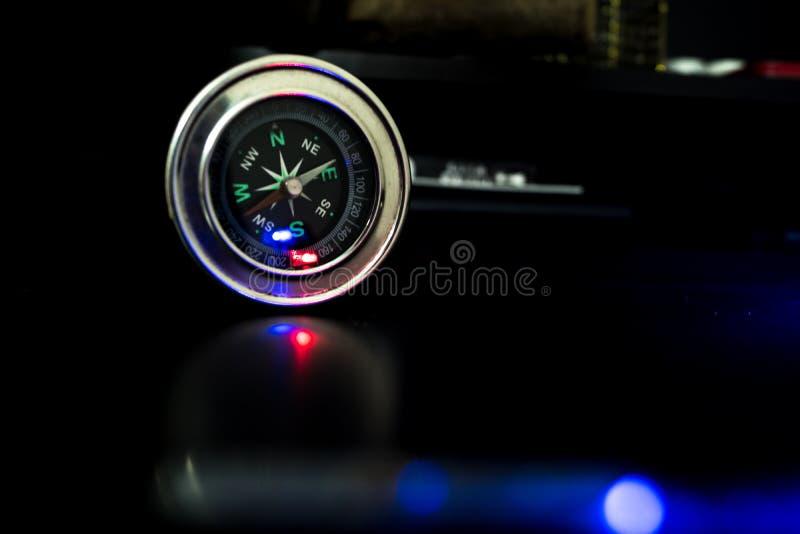 Kompass med blått ljus som faller på det arkivbild