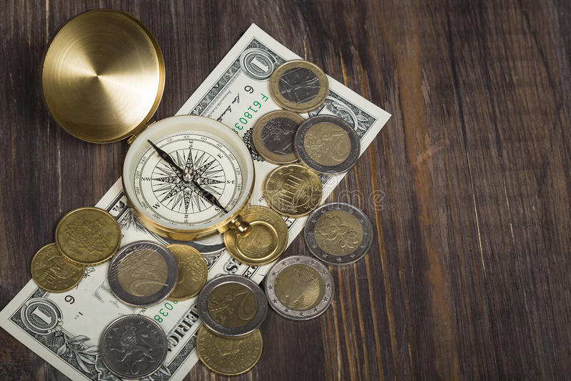 Kompass med euromynt, dollarräkning på träyttersida royaltyfri bild