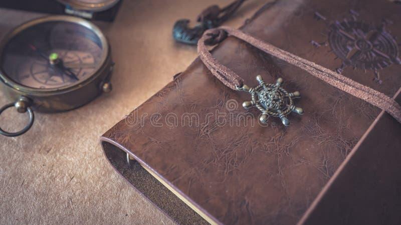 Kompass mit ledernem Taschen-Buch Browns stockfotografie