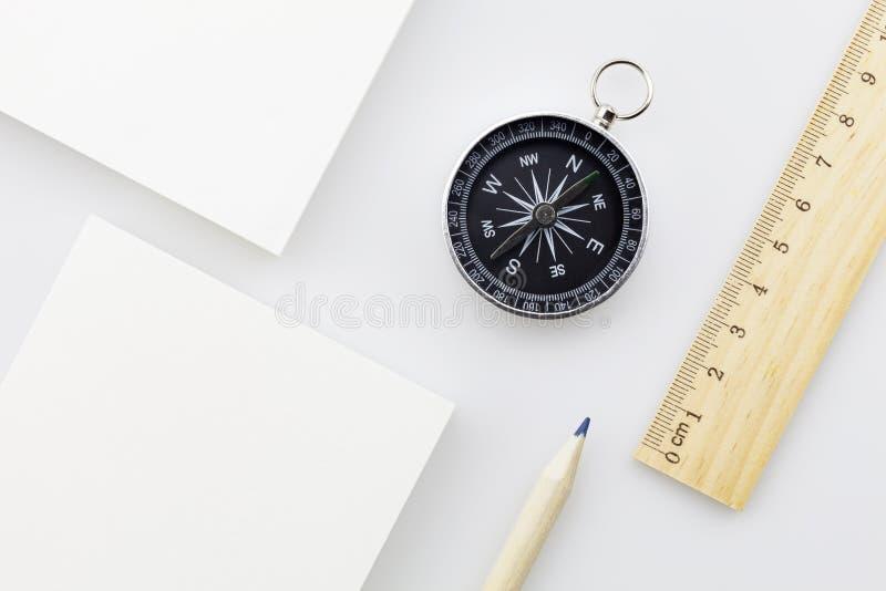 Kompass mit leerem weißem Geschäftspapier, Machthaber, Bleistift auf weißem b lizenzfreie stockfotos
