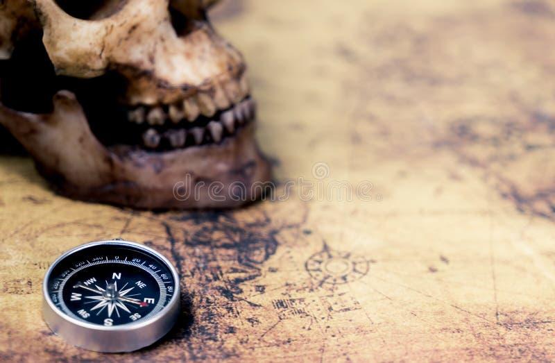 Kompass och död skalle på tappningöversikten för begrepp för skattjägare arkivbilder