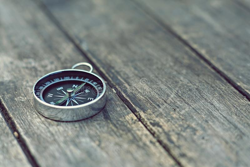 Kompass på gammal trätabellbakgrund, resabegrepp, tappningsignal royaltyfri bild