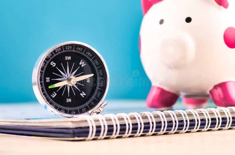 Kompass på kalender över spargrisbakgrund arkivfoto