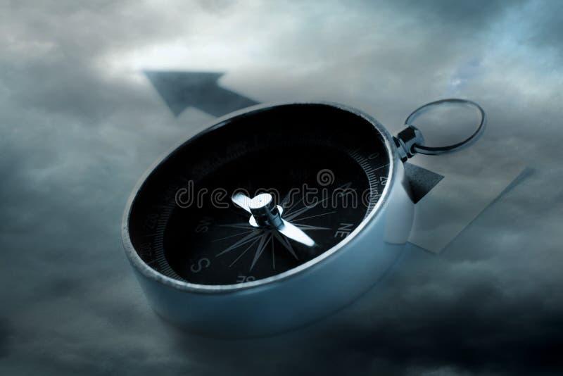 Kompass på mörk molnig himmel arkivbild