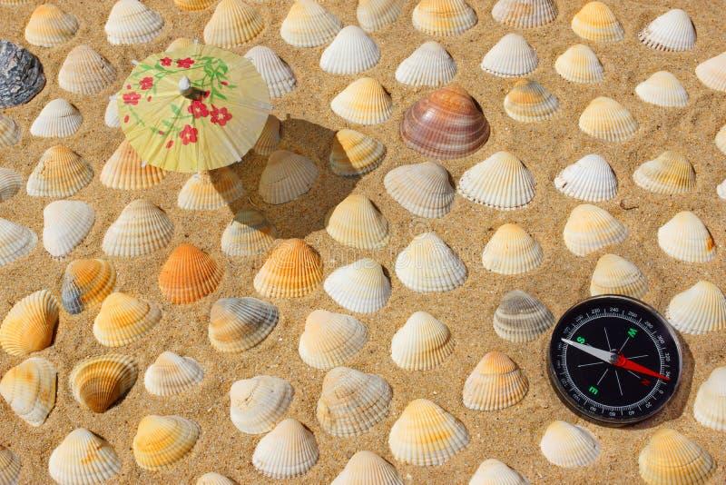 Kompass, paraply och snäckskal arkivfoto