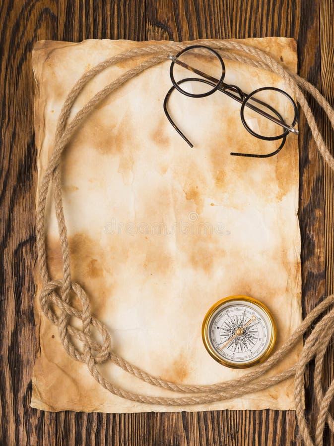 Kompass, rep och exponeringsglas på gammalt papper fotografering för bildbyråer