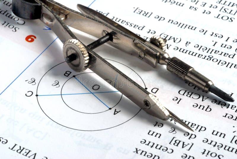 Kompass som vilar på en närbildmatematikövning arkivbild
