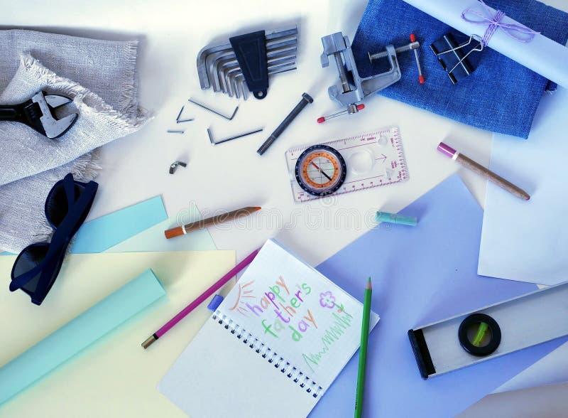 Kompass, Sonnenbrille, Vater ` s Werkzeuge für Reparatur und ein Glückwunschmuster auf einem hellen Hintergrund lizenzfreie stockbilder