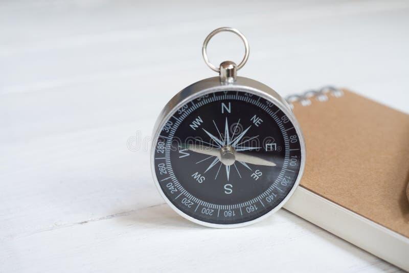 Kompass und braunes Notizbuch auf weißem Holztischhintergrund, Reiseplanungskonzept stockfoto