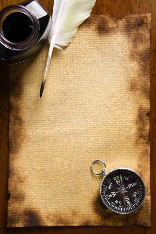 Kompass- und Spulefeder auf altem Papier stockfoto
