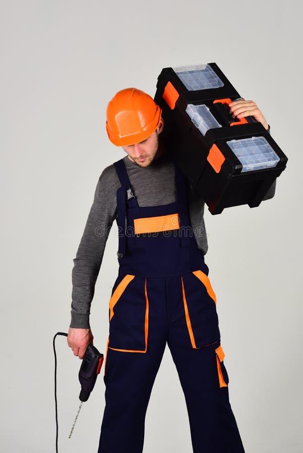 Kompetent arbetare Sats och drillborr för byggnadsarbetarehållreparation Arbeteman eller hård arbetare i arbetskläder Konstruktio arkivbild