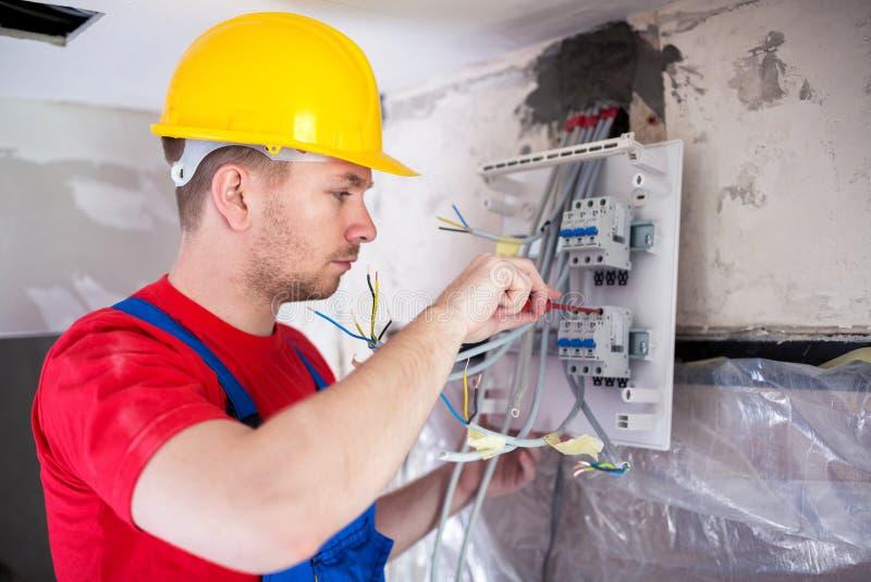 Kompetent arbetare som monterar automatiska strömbrytare på fördelningsbräde royaltyfri foto