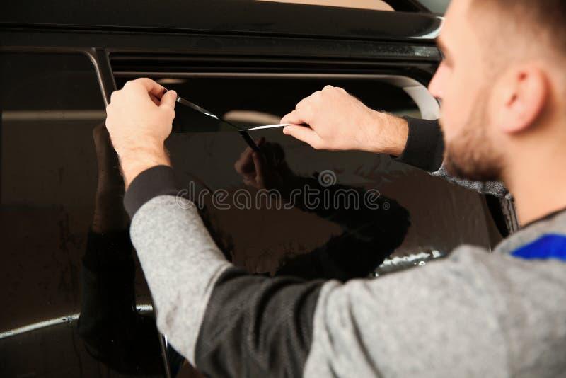 Kompetent arbetare som tonar bilfönstret arkivbild