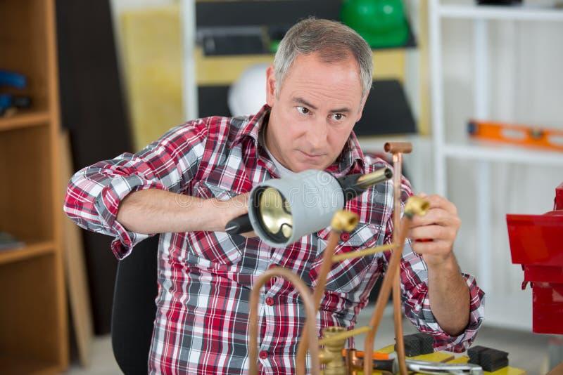 Kompetent detaljhandlare som löder kopparröret fotografering för bildbyråer