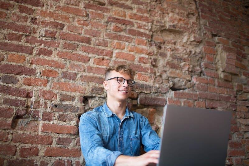 Kompetent freelancer för gladlynt hipsterman som arbetar på bärbar datordatoren i modern inre royaltyfria bilder