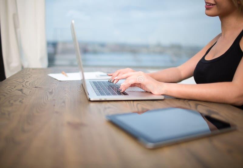 Kompetent freelancer för kvinna eller copywritermaskinskrivningtext på websiten via netto-boken arkivbilder