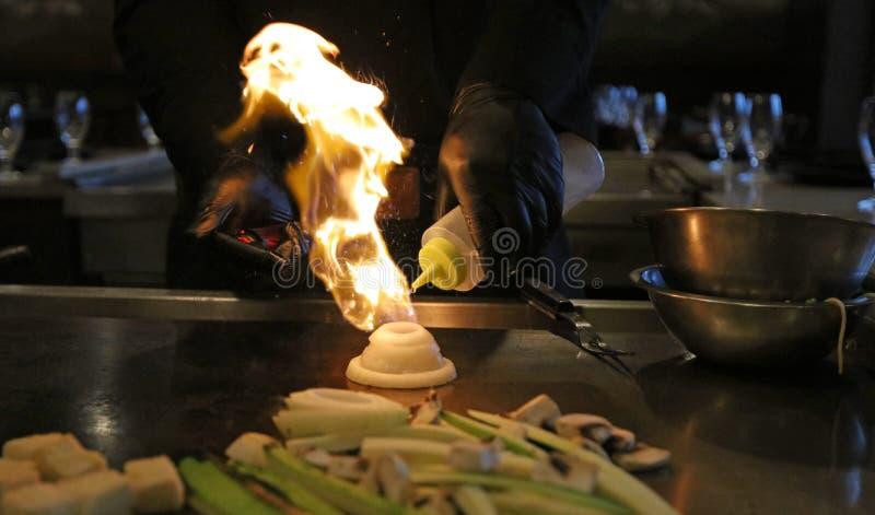 Kompetent japansk kockmatlagning på hibachigallret, artistisk asiatisk mat Stekte ris, grönsaker och nudlar royaltyfri foto