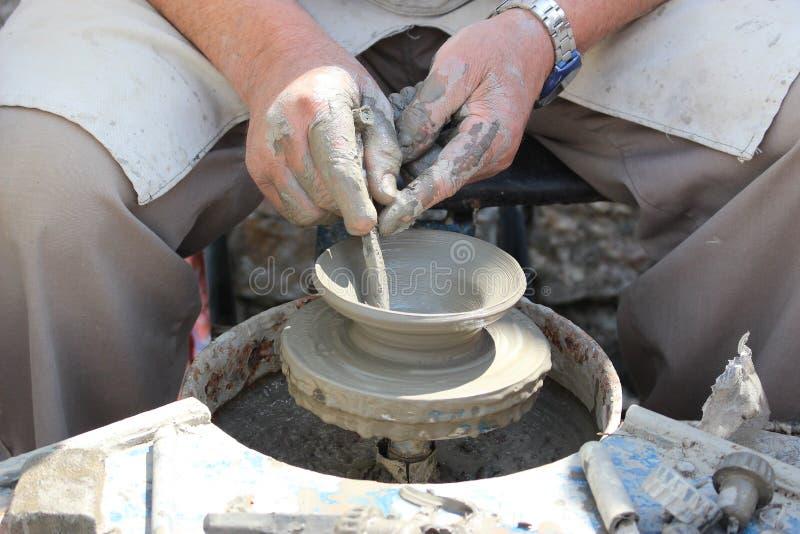 Kompetent keramiker som arbetar med potterÂs hjul - framställning av ett oavslutat stycke av krukmakeri arkivfoto