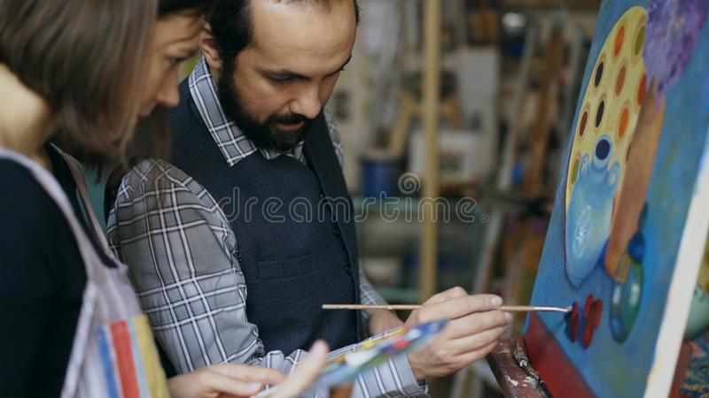Kompetent konstnärlärarevisning och diskuteragrunderna av målning till studenten på konst-grupp royaltyfri bild