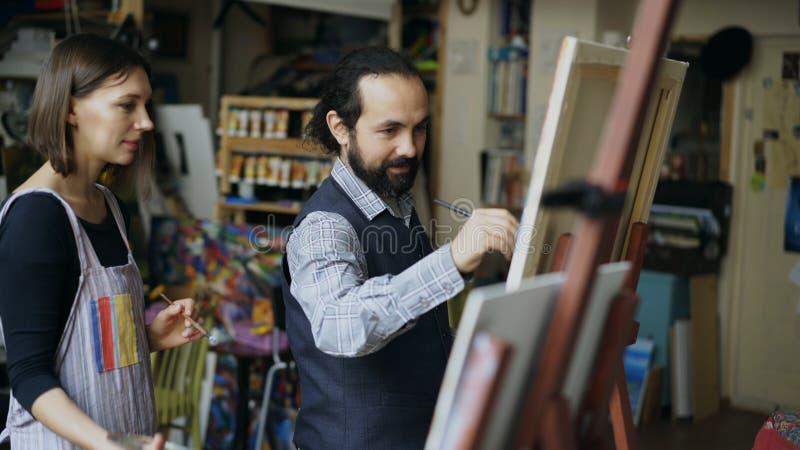 Kompetent konstnärlärarevisning och diskuteragrunderna av målning till studenten på konst-grupp royaltyfri fotografi