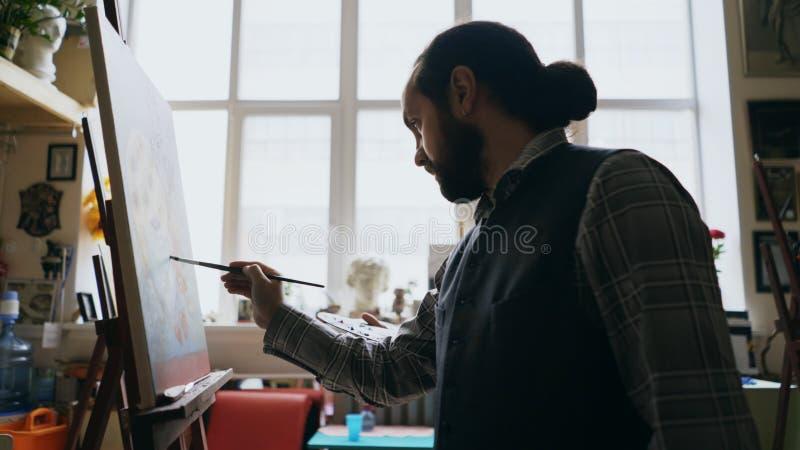 Kompetent konstnärman som undervisar målning för ung kvinna på staffli på studion för konstskola - kreativitet-, utbildnings- och fotografering för bildbyråer