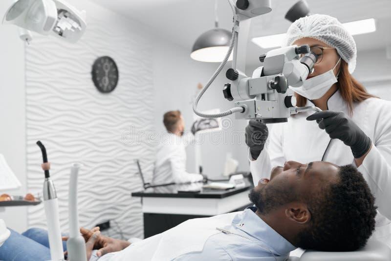 Kompetent kvinnlig doktor i process av att kurera tänder i klinik arkivfoto