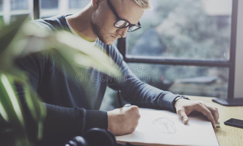 Kompetent märkes- caucasian manteckningsabstrakt begrepp skissar med pennan Process för konstarbete Idérik hobby Notera idéer i k royaltyfri bild