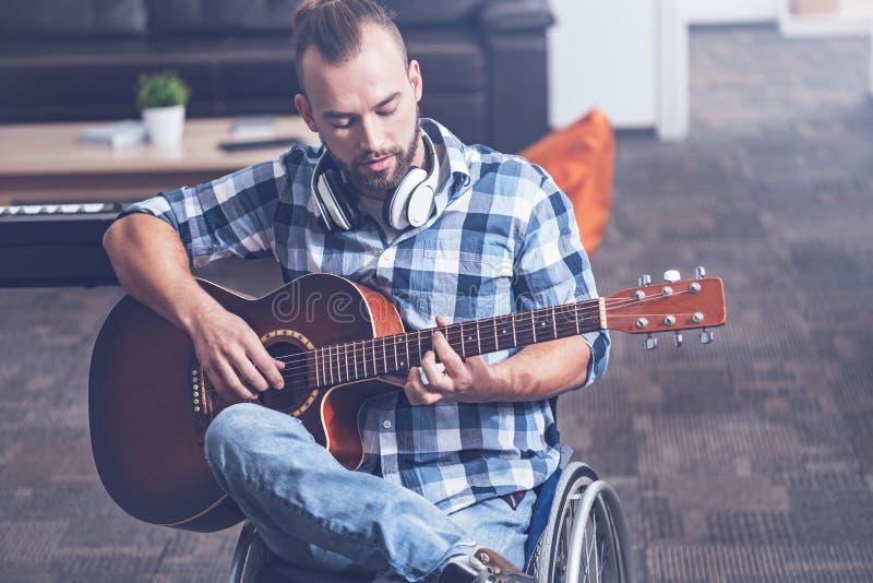 Kompetent man på rullstolen som spelar musikinstrumentet i studion arkivbilder