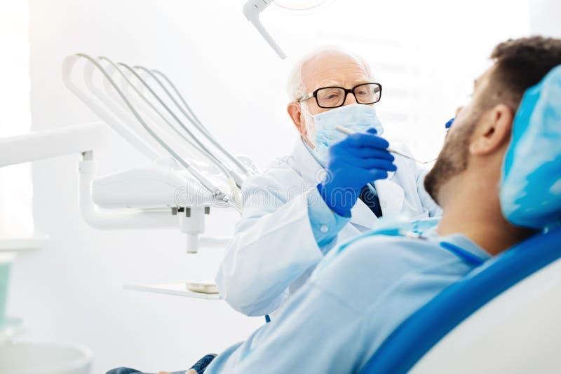 Kompetent stomatologist genom att använda tand- instrument royaltyfria bilder