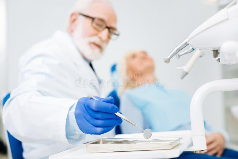 Kompetent tandläkare som ser bort, medan rymma ett hjälpmedel arkivbild