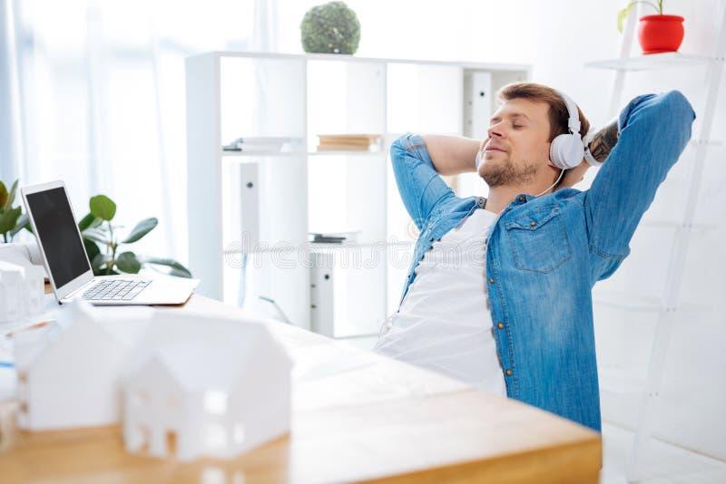 Kompetent tekniker som kopplar av på arbete, medan lyssna till musik royaltyfri fotografi