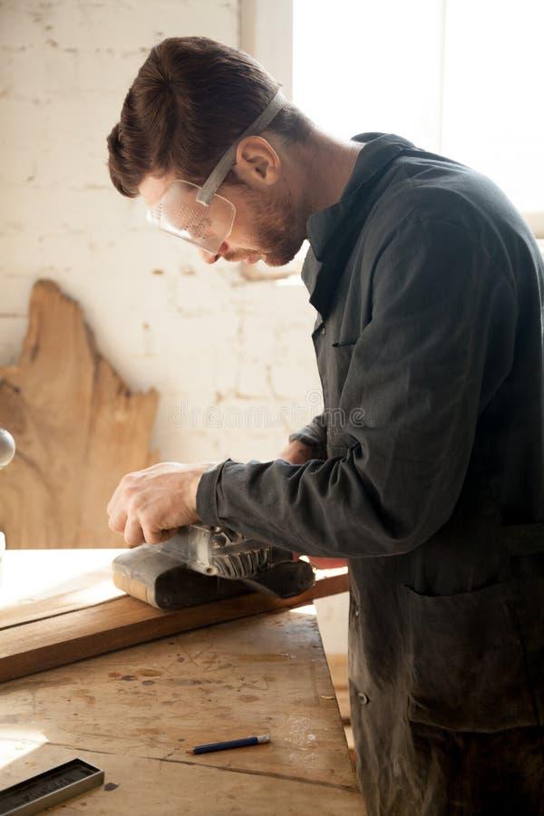 Kompetent ung snickare som gör träverk som arbetar med elkraft sa arkivbild