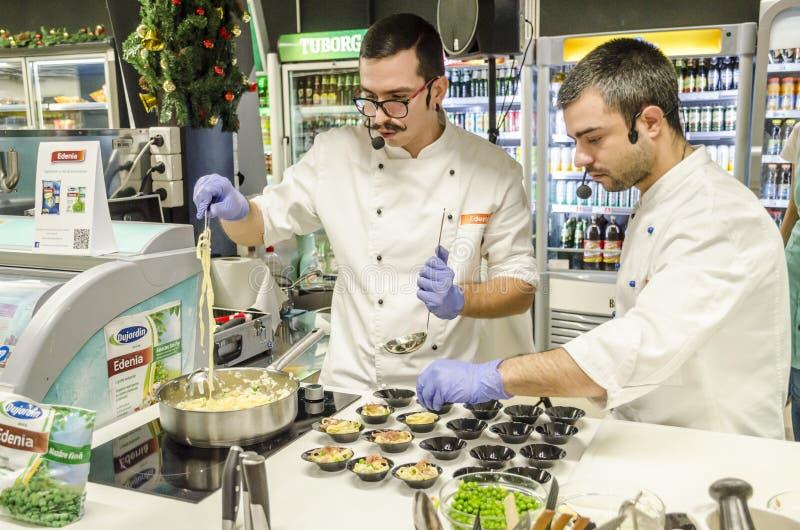 Kompetenta kockar har en matlagningdemonstration arkivfoton