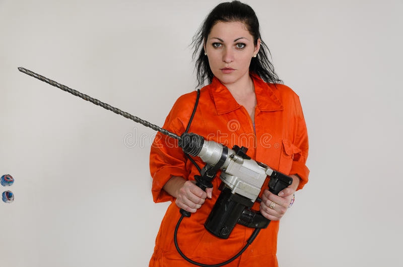 Kompetente Frau mit einem Maurerarbeitbohrgerät stockfoto