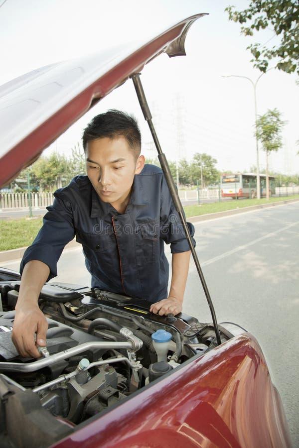 Kompetentny mechanika naprawiania samochód poboczem obraz royalty free