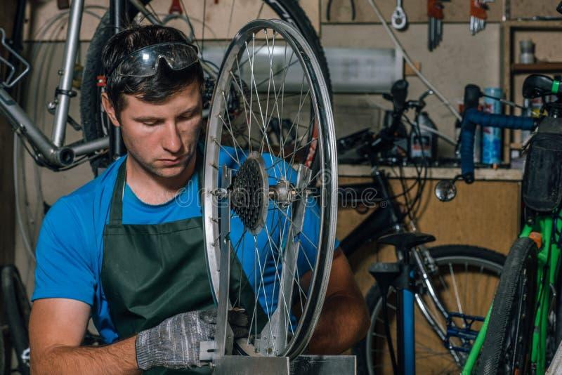 Kompetentny rowerowy mechanik w warsztacie naprawia rower obrazy royalty free