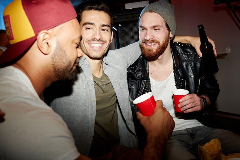 Kompisar som kyler i nattklubben som tycker om partiet arkivbild