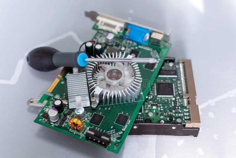 Komponenten einer persönlichen Tischrechnernahaufnahme-Videokarte und des Festplattenlaufwerks mit einem Schraubenzieher im Foto lizenzfreie stockfotos
