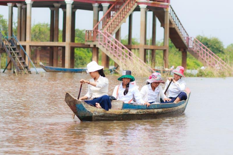 KOMPONG PHLUK, CAMBOYA - 24 DE OCTUBRE: Niños de los barcos de rowing de Kompong Phluk a volver a casa de escuela el 21 de octubr fotos de archivo