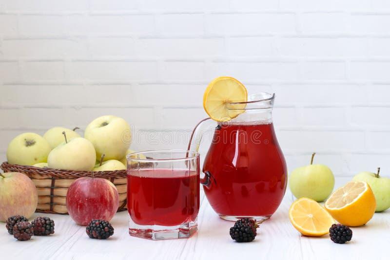 Kompott von Beeren und von Äpfeln in einem Krug und in einem Glas auf einer Tabelle auf einem weißen Hintergrund Im Foto gibt es  stockfoto
