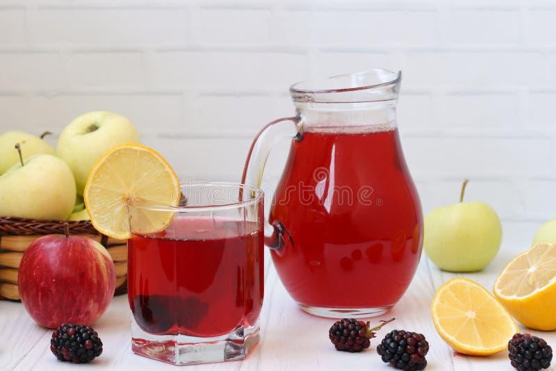 Kompott von Beeren und von ?pfeln in einem Krug und in einem Glas auf einer Tabelle auf einem wei?en Hintergrund Im Foto gibt es  lizenzfreies stockfoto