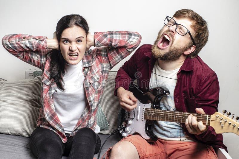Kompozytor gra na gitarze elektrycznej o sześciu łańcuchach i głośno śpiewa piosenkę o swoim składzie, jego dziewczyna nie lubi t obraz stock