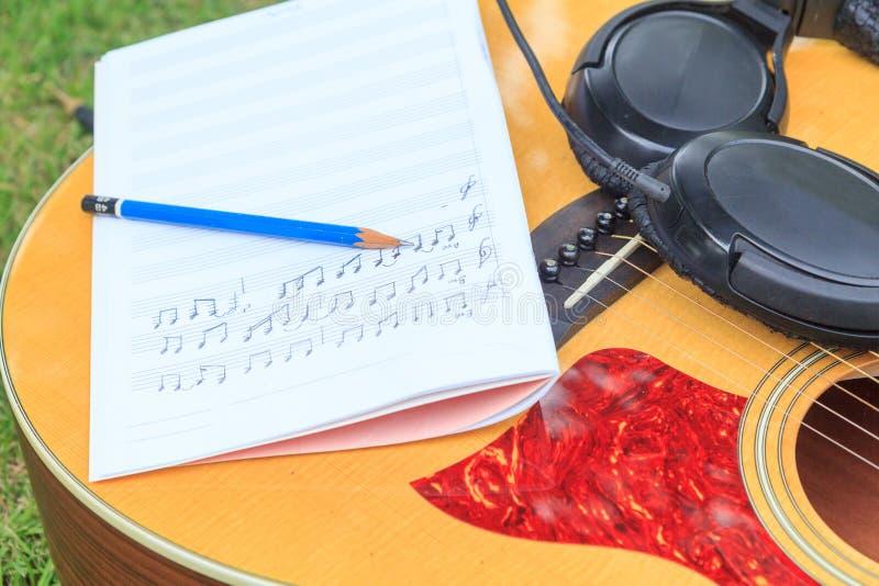 Kompozytor pisze notatce piosenka i używa gitarę akustyczną obraz stock