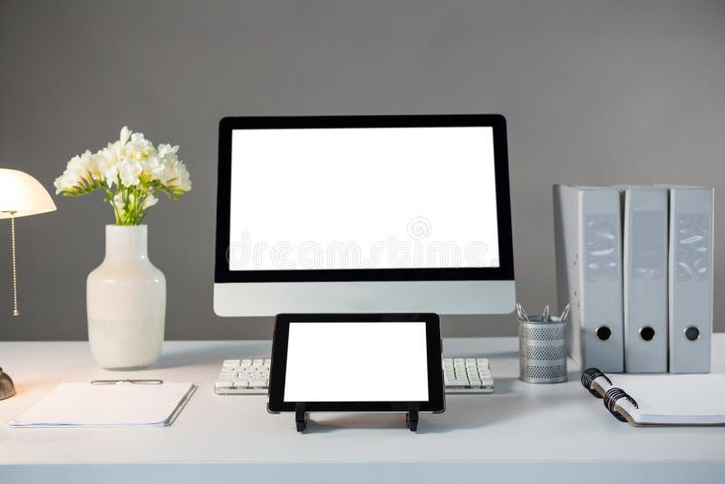 Komputer stacjonarny i cyfrowa pastylka z kwiat wazą obrazy stock